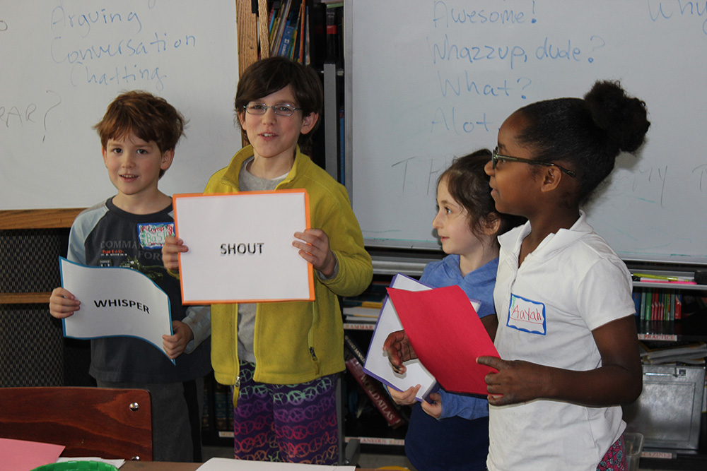 young students smiling and holding word posters