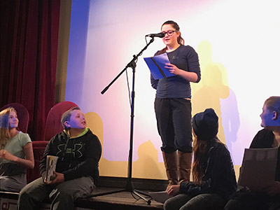 teenage girl reads aloud on stage